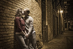 Caucasian couple kissing in brick alley way. Leaning against brick wall; vintage coloring Royalty Free Stock Photos