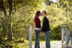 Caucasian couple kissing on outdoor wooden bridge Royalty Free Stock Images