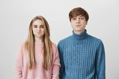Caucasian couple looking at camera blowing their cheeks with positive face expression. Young fair-haired boy and girl stock photo
