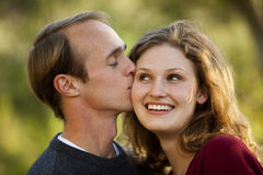 Caucasian couple in love man kissing woman. Caucasian couple smiling in love; man kissing woman on cheek Stock Images