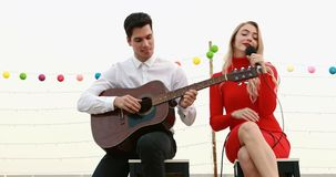 Caucasian couple playing guitar and singing a song stock video