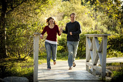 Caucasian couple running on bridge holding hands Stock Photos