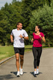 Caucasian couple running in park Stock Photography