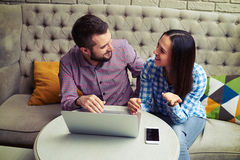 Caucasian couple sitting on sofa and talking Stock Photography