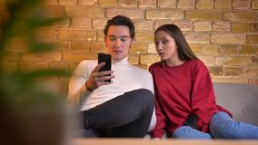 Caucasian couple sitting on sofa watching into smartphone with concentration and talking with each other in home. Atmosphere stock footage