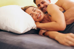 Caucasian couple smiling in bed together Stock Photo