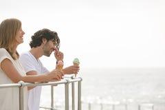 Caucasian couple standing at promenade while having ice cream cone stock photos