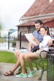 Caucasian Couple Travelling Across the City. Checking Route Using City Map Outdoors. Young Positive Caucasian Couple Travelling Across the City. Checking Route royalty free stock image