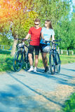 Caucasian Couple Walking With Bicycles in Nature Surroundings Ou Royalty Free Stock Image