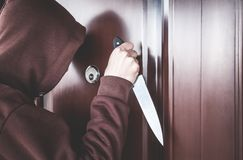 Caucasian criminal with knife looking through the peephole. Royalty Free Stock Photo