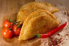 Caucasian cuisine. Cheburek pie on the wood background Royalty Free Stock Photography