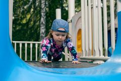 Caucasian cute girl play a slider in Playground in her schoolor kindergarten, kid and fun concept. stock photo