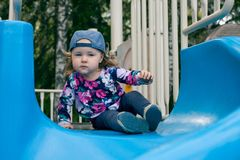 Caucasian cute girl play a slider in Playground in her schoolor kindergarten, kid and fun concept stock photos