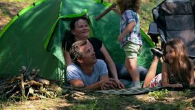Caucasian dad and son assembling tent on holiday outdoors stock footage