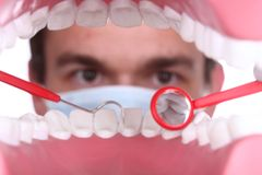 Caucasian Dentist Working Inside a Patient Mouth Stock Image