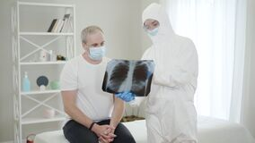 Caucasian doctor in antiviral suit entering hospital ward and showing Covid-19 complications on lungs x-ray to patient