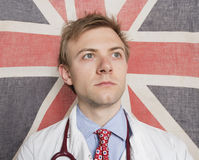 Caucasian doctor looking away with British Flag in background Stock Photography