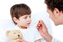 Caucasian doctor taking little boy's temperature Royalty Free Stock Photo