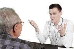 Caucasian doctor talking with aged patient Stock Images