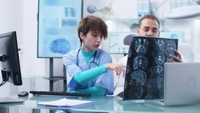 Caucasian doctor and young nurse analyzing MRI scans. In the background - modern research facility with caomputers displaying 3D brain simulations stock footage