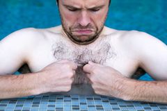 Caucasian dude swimming in pool. he is looking on his hair on chest Stock Images