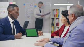 Caucasian elderly couple having consultation in bank. With afro american bank employee about credit terms stock footage