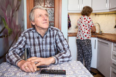 Caucasian elderly husband watches TV in the kitchen, his wife washes dishes Stock Images