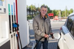 Caucasian elderly man is on gas station with fuelling nozzle inserted in car filler well. Caucasian elderly man is on gas station with a fuelling nozzle inserted Royalty Free Stock Photography