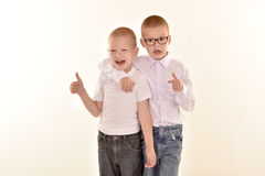A caucasian elementary age boy with glasses posing in uniform isolated on white background with him brother. School and education. Concept stock photos