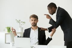 Caucasian employee meditating at workplace ignoring angry boss s. Caucasian employee meditating at workplace ignoring angry african boss scolding him, calm white Royalty Free Stock Photo