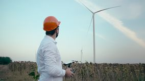 Caucasian engineer with a beard in an orange protective helmet and goggles uses bullets to control a smart quadrocopter stock footage