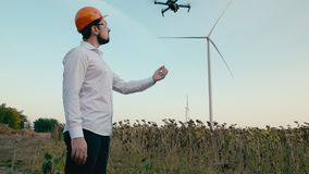 Caucasian engineer in an orange protective helmet and goggles launches from his hand a smart quadcopter drone for stock video
