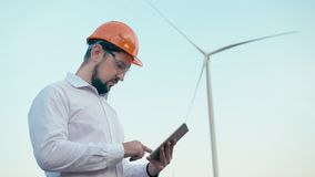 Caucasian engineer in orange protective helmet and goggles uses a tablet against the background of a wind power stock footage