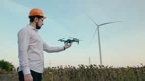 Caucasian engineer in an orange protective helmet puts on goggles and launches a smart quadrocopter drone from his hand stock video footage