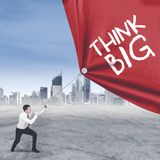 Caucasian entrepreneur pulling text of think big. Caucasian male entrepreneur pulling a banner with text of think big while standing with modern city background Royalty Free Stock Image