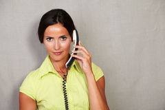 Caucasian ethnicity adult lady holding phone. Caucasian ethnicity adult lady in casual clothing holding phone while looking at camera disappointed on grey Stock Photo