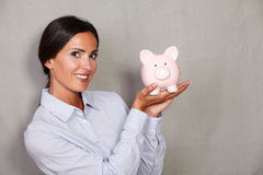 Caucasian ethnicity lady showing piggy bank Stock Photo