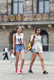 Caucasian and exotic girl, Dam Square, Amsterdam. AMSTERDAM-AUG. 19, 2012. Caucasian and exotic girl walking on the Dam Square on Aug. 19 in Amsterdam. 177 Stock Photos