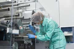 Factory worker work with machine with shafts. Caucasian factory worker in blue lab suit work with manufacture machine with shafts Stock Images
