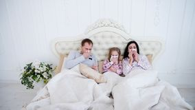 Caucasian fader, moder och liten dotter som nyser med servetter, bärande pyjamas och ligger i säng royaltyfri foto