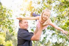 Caucasian fader och dotter som har gyckel på parkera Royaltyfri Bild