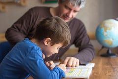 Caucasian fader och son som gör matematikläxa Arkivfoto