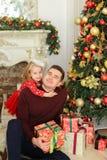 Caucasian fader som sittling med spisen och julgranen för liten dotter som den near dekorerade håller gåvor Royaltyfri Foto