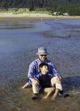 Caucasian fader som spelar i vatten på stranden med den rörelsehindrade sonen Royaltyfria Foton