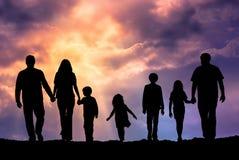 Caucasian familj som är utomhus- på solnedgången Arkivfoto