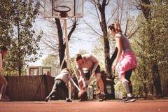 Caucasian familj som spelar basket tillsammans Arkivbilder