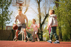 Caucasian familj som spelar basket tillsammans Arkivfoton
