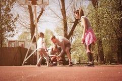 Caucasian familj som spelar basket tillsammans Arkivfoto