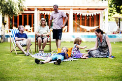 Caucasian familj som tillsammans tycker om sommar på trädgården arkivfoto