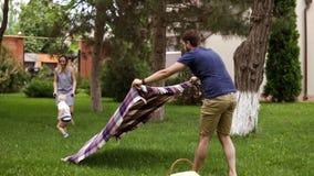 Caucasian familj utomhus Fader, moder och liten blondy son Farsan fördelar en picknickräkning, picknickkorg grön lawn lager videofilmer